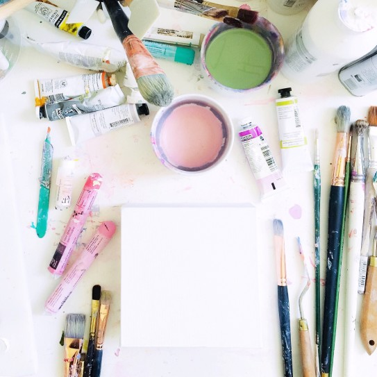 looking-down-at-an-artists-messy-white-desktop-with-art-supplies-and-a-blank-canvas_t20_AemJdW